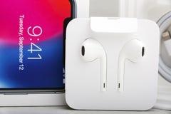特拉维夫,以色列- 2017年11月23日:有充电器和耳机的Iphone x巧妙的电话 最新苹果计算机Iphone 10手机 库存图片