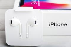 特拉维夫,以色列- 2017年11月23日:有耳机的Iphone x巧妙的电话 最新苹果计算机Iphone 10手机 库存图片