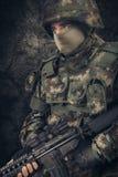 特种部队战士人举行在黑暗的背景的机枪 免版税图库摄影