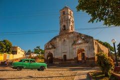 特立尼达,古巴:老被破坏的天主教 老减速火箭的绿色汽车 免版税图库摄影