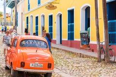 特立尼达,古巴- 2017年5月16日:在城市街道上的橙色减速火箭的汽车 复制文本的空间 库存照片