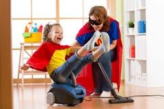 特级英雄在吸尘器的孩子飞行 清洗屋子的母亲和儿童女儿和获得一个乐趣 免版税图库摄影