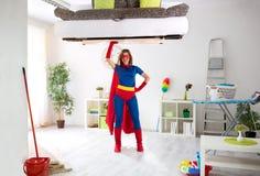 特级英雄妇女准备好清洗的房子 免版税库存照片