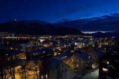 特罗姆瑟市在与光、交通、海湾和行动的冬天多雪的晚上与大陆 免版税库存照片