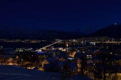 特罗姆瑟市在与光、交通、海湾和行动的冬天多雪的晚上与大陆 免版税库存图片