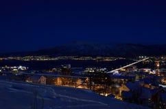特罗姆瑟市在与光、交通、海湾和行动的冬天多雪的晚上与大陆 库存图片