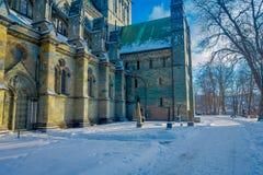 特隆赫姆,挪威- 2018年4月04日:冬天驻地的Nidaros大教堂Nidarosdomen与在街道的雪 库存图片
