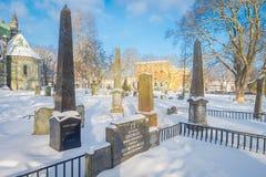 特隆赫姆,挪威- 2018年4月04日:用雪盖的墓碑室外看法在冬天驻地时在Nidaros 免版税库存图片