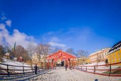 特隆赫姆,挪威- 2018年4月04日:走在一个老木桥与一些木材的Gamle Bybro的室外观点的人 免版税库存图片