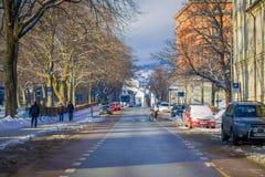 特隆赫姆,挪威- 2018年4月04日:走在接近停放的有些汽车的一条边路的室外观点的未认出的人民 库存图片