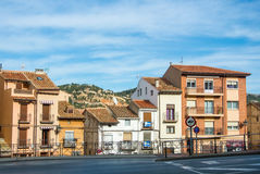 特鲁埃尔省,西班牙- 2016年2月01日:有瓦屋顶的议院在背景的路和黏土小山,特鲁埃尔省街道附近  库存图片