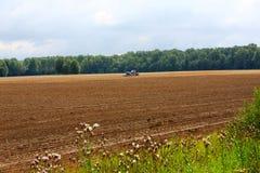 犁与红色拖拉机的农夫亩茬地 库存照片