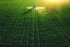犁和喷洒在领域的农用拖拉机鸟瞰图 免版税库存照片