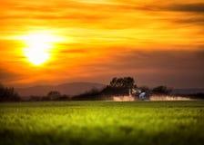 犁和喷洒在日落的农用拖拉机 免版税库存照片