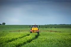 犁和喷洒在麦田的农用拖拉机 免版税库存照片