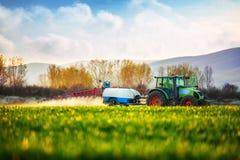 犁和喷洒在绿色领域的农用拖拉机 免版税库存照片