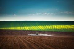 犁喷洒的拖拉机的农田 免版税库存照片