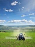 犁喷洒的拖拉机的农田 免版税库存图片