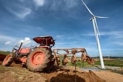 犁在有风轮机干净的ener的种植园农场的拖拉机 免版税库存图片
