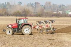 犁在秋天的红色拖拉机 免版税库存照片