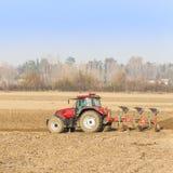 犁在秋天的红色拖拉机 图库摄影