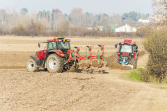 犁在秋天的红色拖拉机 库存照片