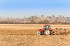 犁在秋天的红色拖拉机 免版税库存图片