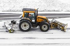 犁拖拉机机器的大雪在路的工作在雪风暴期间在冬天 库存图片