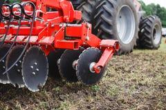 犁现代技术红色拖拉机关闭在一个农业领域机制 免版税库存图片
