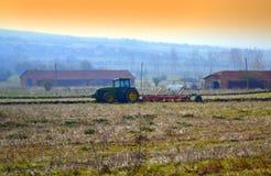犁秋天日落领域的拖拉机 免版税库存图片