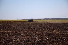 犁耕地的被转动的拖拉机 图库摄影