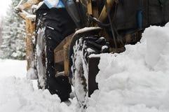 犁雪的拖拉机 库存照片