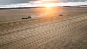 犁领域的两台拖拉机在日出 农业视图航拍 免版税图库摄影