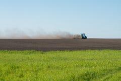 犁领域的蓝色拖拉机 免版税库存照片