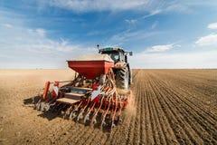 犁领域-的拖拉机土地为播种在秋天做准备 免版税库存图片