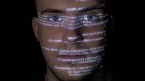 犯罪一危险黑客的网络的画象看照相机,当跑的编程的代码在他的面孔被射出-时 股票视频