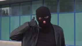 犯罪人窃贼或强盗面具陈列电话姿态的由他的手指 股票视频