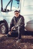 犯罪出现的一个年轻人在黑皮夹克的 免版税图库摄影