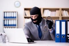 犯罪商人佩带的巴拉克拉法帽在办公室 免版税库存照片