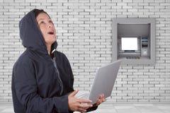 犯罪在使用一台膝上型计算机的妇女黑客佩带的敞篷在前面 免版税库存图片