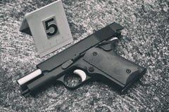 犯罪现场调查、手枪和子弹壳与血迹反对罪行标志 库存照片