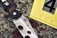 犯罪现场调查、血淋淋的刀子和受害者` s鞋子有犯罪标志的在地面,杀人证据 免版税库存图片