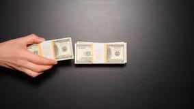 犯罪-商人偷窃从堆的金钱在台式视图 库存照片