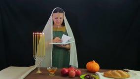 犹太人的妇女读一个祷告以纪念犹太新年 附近的烧伤蜡烛 股票录像