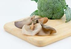 犹太人的耳朵蘑菇硬花甘蓝和芦笋在切板isola 免版税库存照片