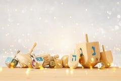 犹太假日光明节横幅与木dreidels & x28的; 转动的top& x29;在闪烁发光的背景 库存照片