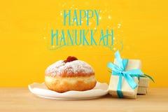 犹太假日光明节的图象与当前箱子和传统多福饼的在桌上