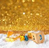 犹太假日光明节的图象与木五颜六色的dreidels (抽陀螺)的和在12月的巧克力传统硬币下雪 图库摄影