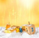 犹太假日光明节的图象与木五颜六色的dreidels (抽陀螺)的和在12月的巧克力传统硬币下雪 免版税库存照片