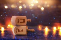犹太假日光明节的图象与木dreidels收藏& x28的; 转动的top& x29;并且发光的金光 图库摄影